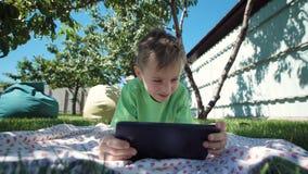 Junge, der mit Tablette im Garten sich verständigt stock video footage
