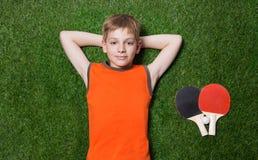 Junge, der mit Tennisschläger auf grünem Gras liegt Lizenzfreie Stockbilder
