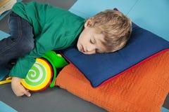 Junge, der mit Toy In Kindergarten schläft stockbild