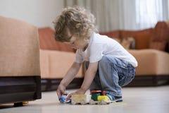Junge, der mit Toy Train In Living Room spielt lizenzfreie stockfotos