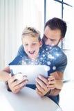 Junge, der mit Vater am Tisch sitzt und PC-Tablette im modernen Dachboden verwendet Kindheit träumt Ikonenkonzept vertikal Lizenzfreies Stockfoto