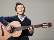 Junge, der mit Vergnügen auf Akustikgitarre spielt stockbild