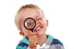 Junge, der mit Vergrößerungsglas sucht stockbilder