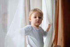 Junge, der mit Vorhängen spielt Stockbild