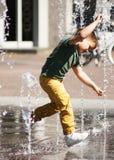 Junge, der mit Wasser spielt Lizenzfreies Stockbild