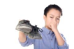 Junge, der mit Weißsocke des schlechten Geruchs unglücklich sich fühlt Stockfoto