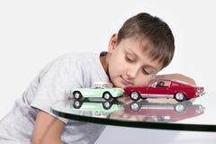 Junge, der mit zwei Spielzeugautos spielt Lizenzfreies Stockfoto