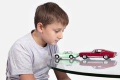 Junge, der mit zwei Spielzeugautos spielt Lizenzfreie Stockfotos