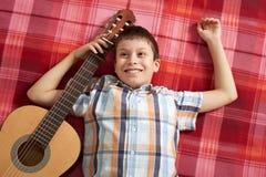 Junge, der Musik auf Gitarre, Lügen auf einer roten karierten Decke, Draufsicht spielt Lizenzfreie Stockfotos