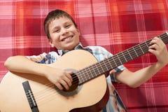 Junge, der Musik auf Gitarre, Lügen auf einer roten karierten Decke, Draufsicht spielt Lizenzfreies Stockbild