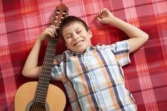 Junge, der Musik auf Gitarre, Lügen auf einer roten karierten Decke, Draufsicht spielt Stockfotos
