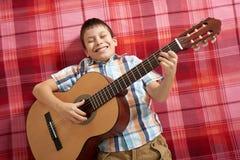 Junge, der Musik auf Gitarre, Lügen auf einer roten karierten Decke, Draufsicht spielt Lizenzfreie Stockbilder