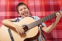 Junge, der Musik auf Gitarre, Lügen auf einer roten karierten Decke, Draufsicht spielt Lizenzfreies Stockfoto