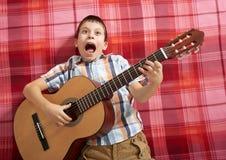 Junge, der Musik auf Gitarre, Lügen auf einer roten karierten Decke, Draufsicht spielt Stockfotografie