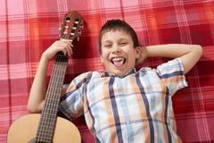 Junge, der Musik auf Gitarre, Lügen auf einer roten karierten Decke, Draufsicht spielt Stockbilder