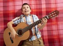 Junge, der Musik auf Gitarre, Lügen auf einer roten karierten Decke, Draufsicht spielt Lizenzfreie Stockfotografie