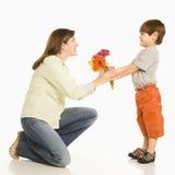 Junge, der Mutterblumen gibt. Stockfotografie