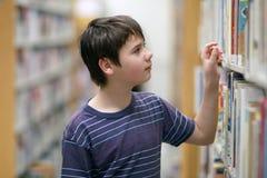 Junge, der nach Bibliotheksbuch sucht Lizenzfreie Stockfotografie