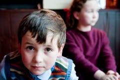 Junge, der nach Kamera, Mädchen untersucht Lizenzfreie Stockbilder