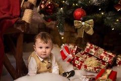 Junge, der nahe bei einem Weihnachtsbaum mit vielen Geschenken sitzt Stockfotografie