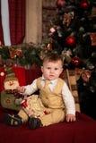 Junge, der nahe bei einem Weihnachtsbaum sitzt Lizenzfreie Stockfotografie