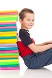 Junge, der nahe bei Stapel Büchern sitzt Stockfotografie
