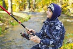 Junge, der nahe Fluss fischt Stockbild