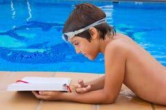 Junge, der nahe Pool liest Stockfoto