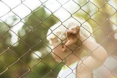 Junge, der nahen Ineinander greifenzaun steht Lizenzfreies Stockbild