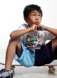 Junge, der oben beim Sitzen auf seinem Skateboard schaut Stockbilder
