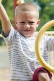 Junge, der oben Dschungel-Turnhalle auf Playscape klettert Stockfotos