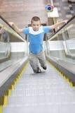 Junge, der oben durch Rolltreppe läuft Lizenzfreies Stockfoto