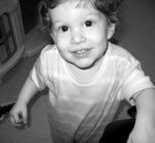 Junge, der oben mit einem Grinsen schaut stockbild