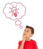 Junge, der oben schaut und mit Glühlampe in den Blasen denkt Lizenzfreie Stockfotos