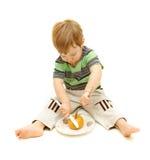 Junge, der Orange mit Gabel und Messer schneidet Stockfotos