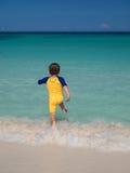 Junge, der in Ozean läuft Lizenzfreies Stockfoto