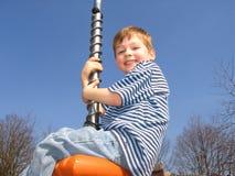 Junge, der am Park spielt Stockbild