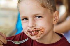 Junge, der Pfannkuchen mit Banane und Schokolade isst Lizenzfreies Stockfoto