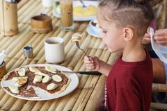 Junge, der Pfannkuchen mit Banane und Schokolade isst Lizenzfreie Stockfotos
