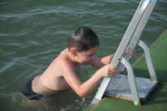 Junge an der Pierstrichleiter stockfotografie