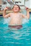 Junge, der in Pool spritzt Stockfotos