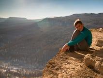 Junge, der am Rand der Klippe sitzt Stockbilder