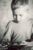 Junge, der Retro- Kamera mit Interesse überprüft stockfotos