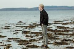 Junge, der in Richtung des Meeres während der Ebbe blickt Lizenzfreie Stockbilder