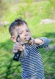 Junge, der Riemen-Schuss auf Kamera abzielt stockfoto