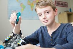 Junge, der Roboter-Kit In Bedroom zusammenbaut stockfoto
