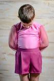 Junge, der rosa Tanz-Ausstattung mit dem Kopf gebeugt trägt Stockbild