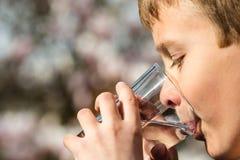 Junge, der Süßwasser vom Glas trinkt Stockbilder