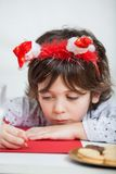 Junge, der Santa Headband Writing Letter To Sankt trägt Lizenzfreie Stockfotos