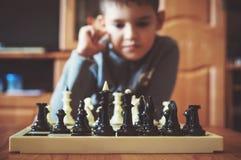 Junge, der Schach im Kind-` s Raum spielt lizenzfreies stockfoto